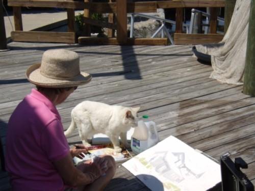 Carol painting plein air with a little help from a friend, Cedar Key.
